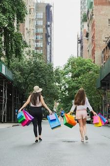 Frauen gehen auf der straße mit einkaufstüten