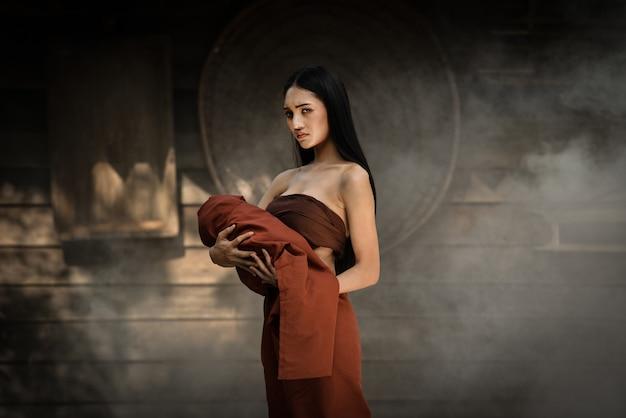 Frauen-geisterdrama und tragen ihres babygeistes, das auf altem thailändischem haus steht