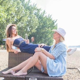 Frauen genießen auf dem liegestuhl über dem strand