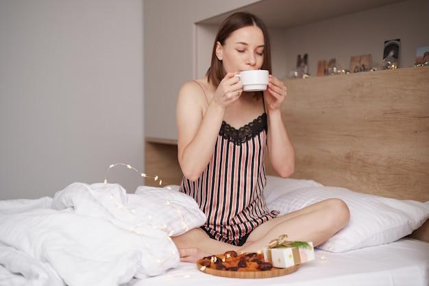 Frauen genießen kaffee mit marshmallows auf dem bett mit geschenk in ihrer nähe.
