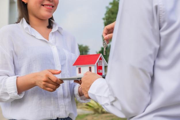 Frauen glückliches neues zuhause, das immobilien kauft, hand, die das hauslächeln hält