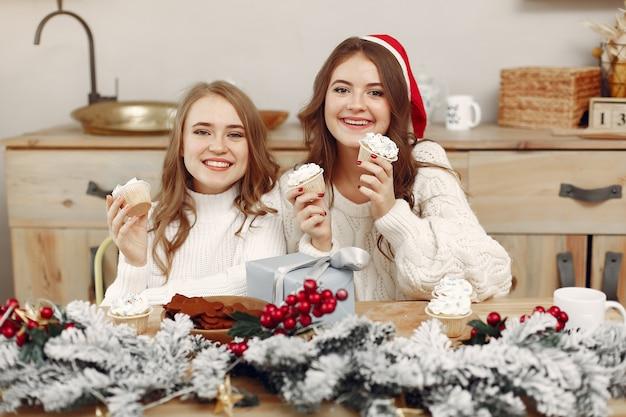 Frauen haben cupcakes. freunde in einer weihnachtsdekoration. mädchen in einer weihnachtsmannmütze.