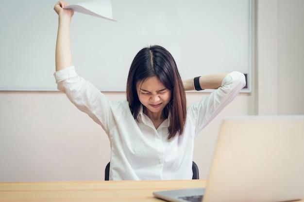 Frauen haben rückenschmerzen wegen des computers und arbeiten für eine lange zeit.