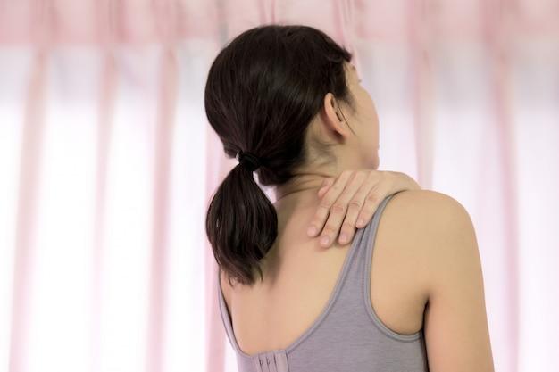 Frauen haben schulterschmerzen und halten die hand am muskel.