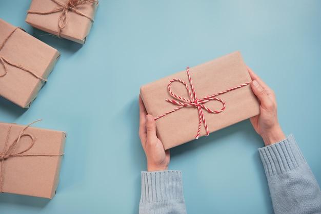 Frauen-hände, die kraftpapiergeschenkbox auf blauem hintergrund halten. für anwesende weihnachten, neues jahr, valentinstag oder jahrestag.