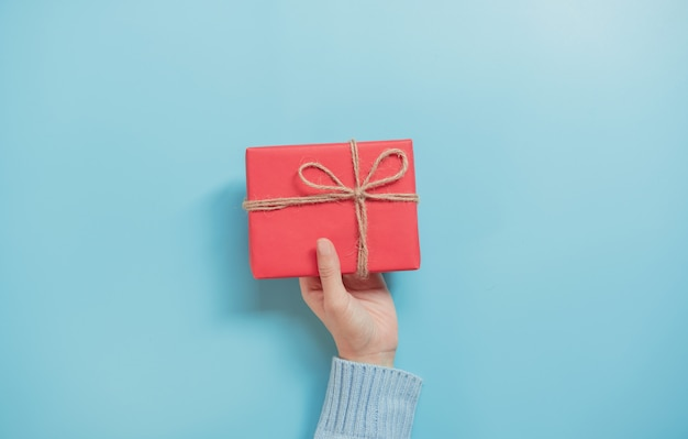 Frauen-hände, die kraftpapiergeschenkbox auf blauem hintergrund- und kopienraum halten. für anwesende weihnachten, neues jahr, valentinstag oder jahrestag.