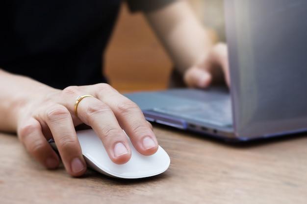 Frauen-hände, die laptop und drahtlose maus verwenden