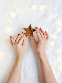 Frauen-hände, die weihnachten toy decor wooden star new year halten