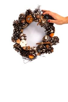 Frauen-hände, die weihnachtskranz halten