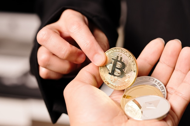 Frauen halten die kryptowährungsmünze zur hand.