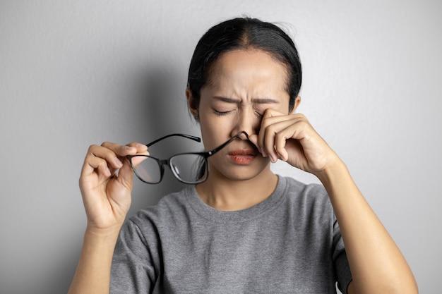 Frauen halten eine brille und leiden unter augenschmerzen.