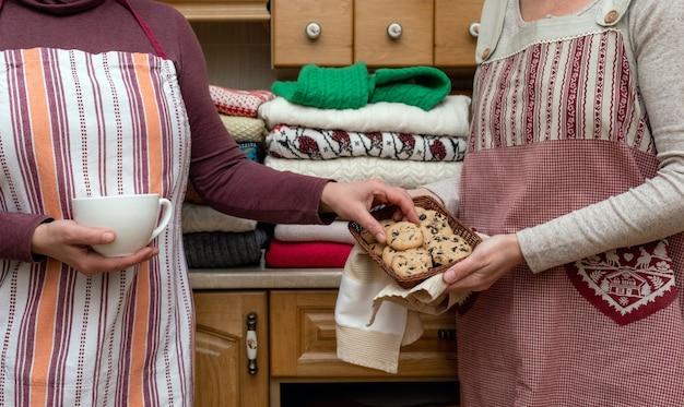 Frauen halten eine tasse kaffee und kekse in festlichen schürzen mit vielen verschiedenen pullovern in der küche.
