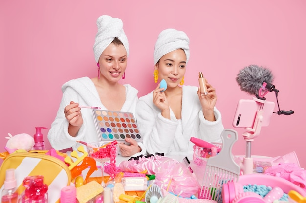 Frauen halten lidschatten-palette und eine flasche foundation sprechen über professionelles make-up online-video aufnehmen haben eigenen blog in bademänteln handtücher auf dem kopf.
