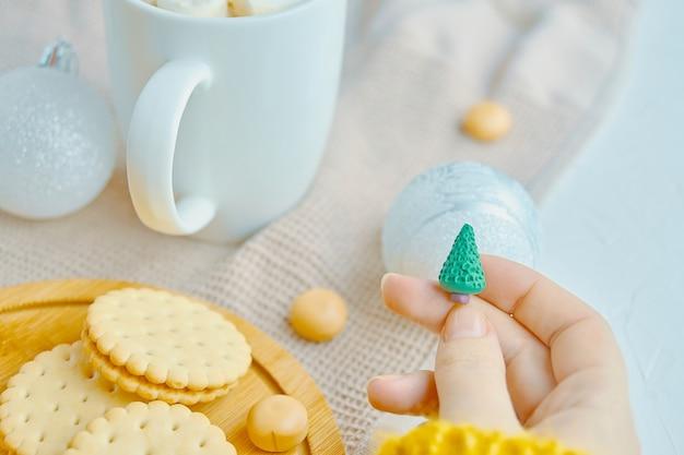 Frauen halten weihnachtsspielzeug in der hand weiße becherkekse und süßigkeiten auf einem tablett und eine tischdecke auf dem ...