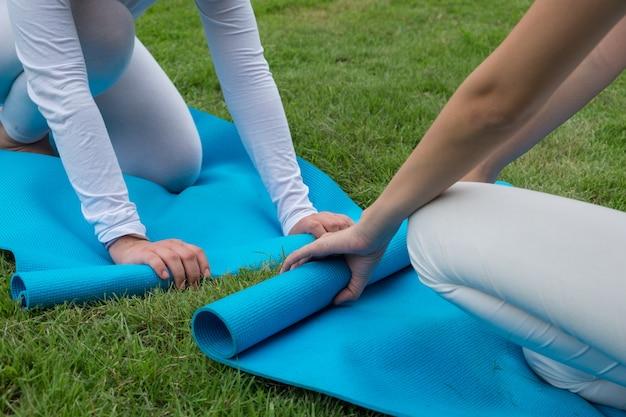 Frauen halten yogamatte nach dem yoga-kurs