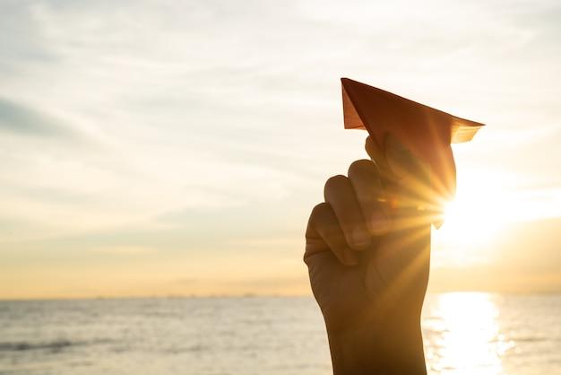 Frauen-hand, die rote papierrakete mit hintergrund des blauen himmels während des sonnenuntergangs hält