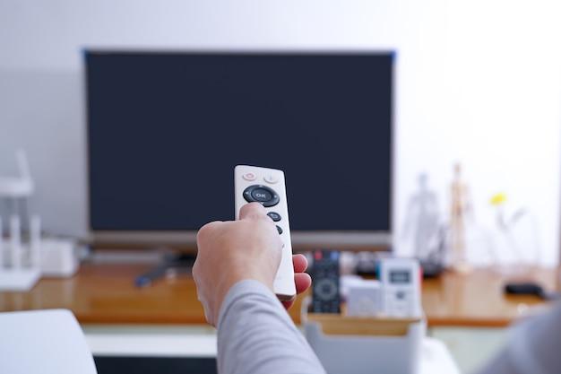 Frauen hand halten fernbedienung tv-box