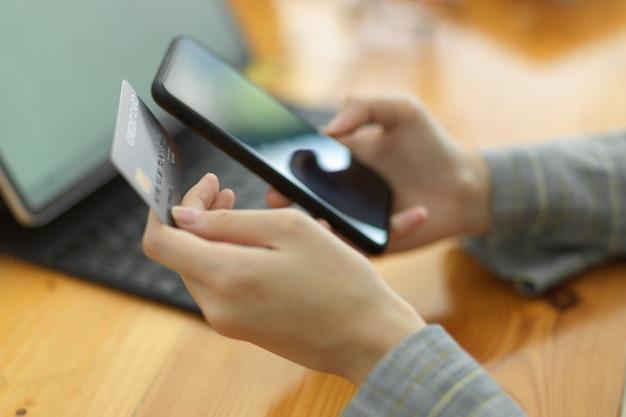 Frauen hand halten smartphone und kreditkarte bezahlen rechnungen online-shopping überweisung geld