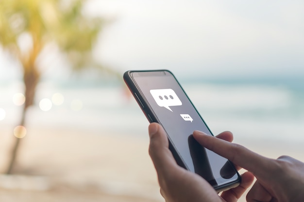 Frauen hand mit smartphone-eingabe, chat-konversation in chat-box und symbole social media app popup. technologischer hintergrund.
