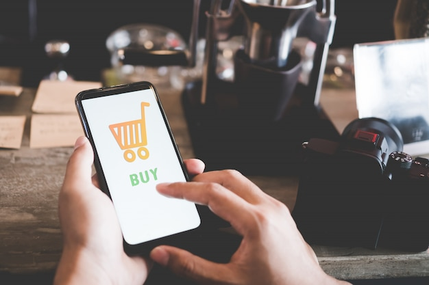 Frauen hand mit smartphone machen online-geschäft oder online-shopping in schwarzen freitag mit warenkorb, dollar-symbole erscheinen im öffentlichen bereich