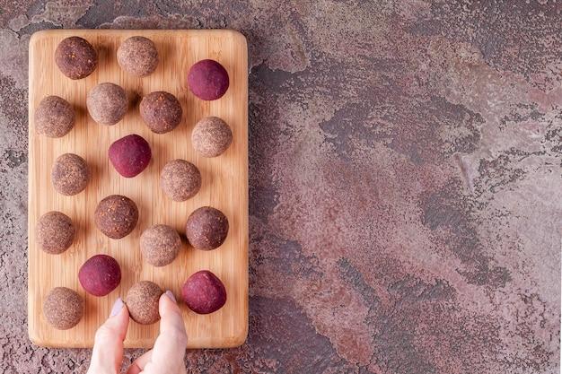 Frauen-hand nehmen selbst gemachte rohe kakao-energie-bälle des strengen vegetariers vom hölzernen brett