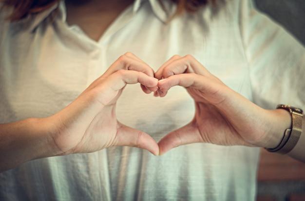 Frauen handgemacht in form von herzen und auf der brust mit liebe, hand in form eines herzens der liebe.