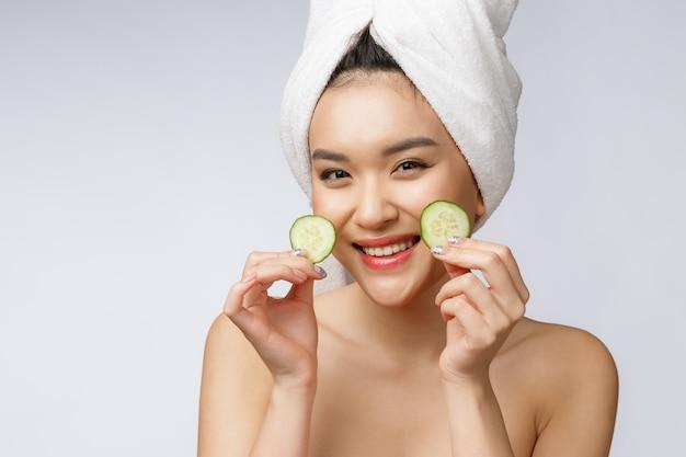 Frauen-hautpflegebild der schönheit junge asiatische mit gurke auf weißem hintergrundstudio.