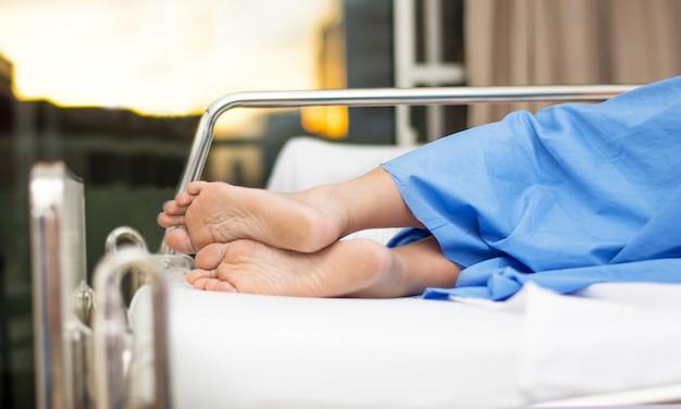 Frauen hinken morgens auf einem weißen bettraum im krankenhaus oder im gesundheitswesen zurück gesundheits- und medizinkonzept