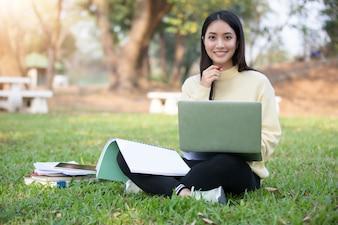 Frauen-Hochschulstudenten, die auf dem grünen Gras arbeiten und lesen lächeln und sitzen