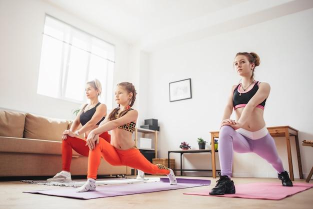 Frauen hocken und strecken die beine und machen kniebeugenübungen, die an den po-muskeln arbeiten.