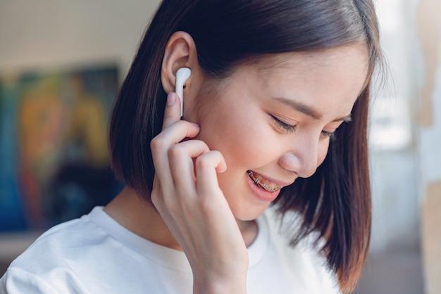 Frauen hören musik aus weißen kopfhörern.