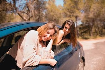 Frauen im Auto, das Kamera betrachtet