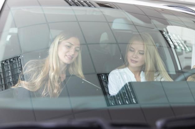 Frauen im auto, das klemmbrett betrachtet