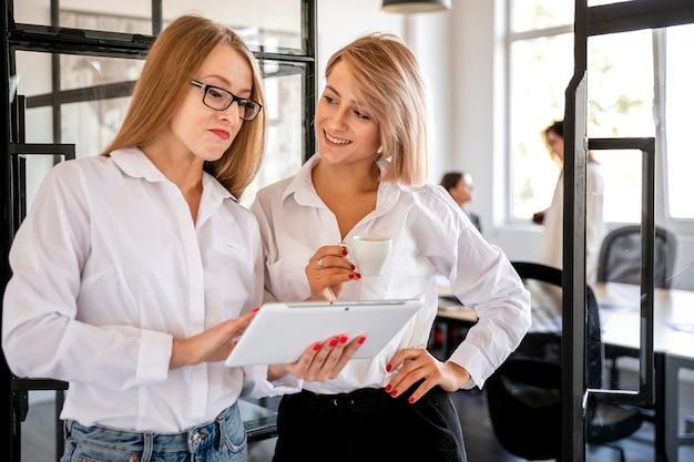 Frauen im büro, das an tablette arbeitet