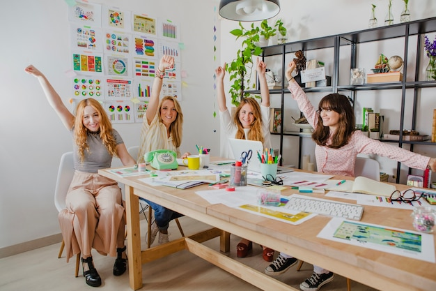 Frauen im büro mit den händen hoch