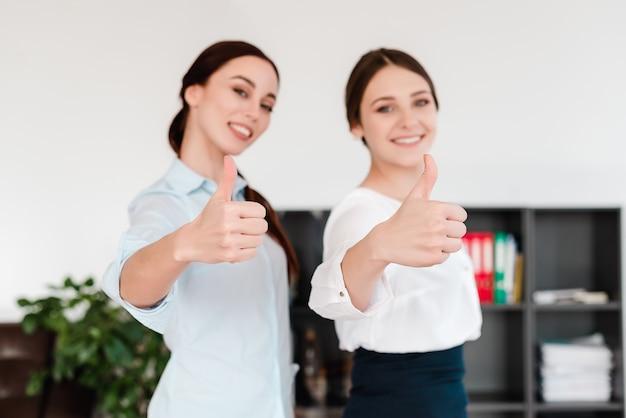 Frauen im büro zeigen daumen hoch im fokus