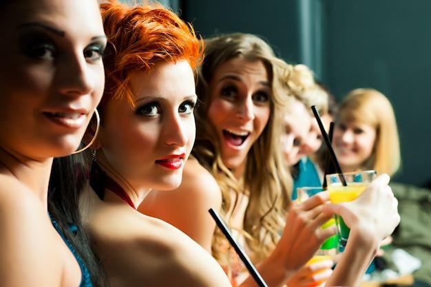 Frauen im club oder in der disco trinken cocktails