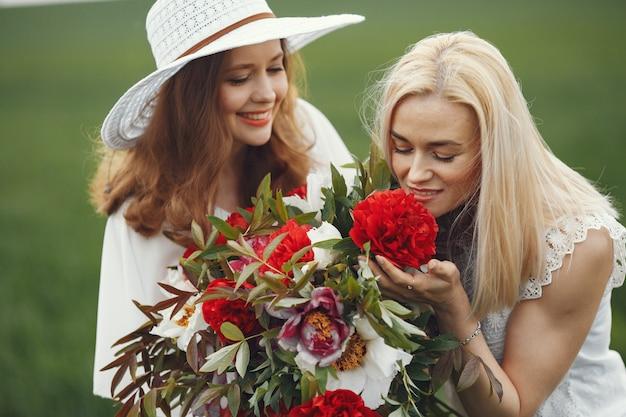 Frauen im eleganten kleid stehen in einem sommerfeld
