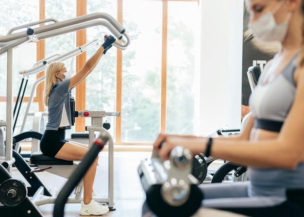 Frauen im fitnessstudio mit geräten mit medizinischer maske