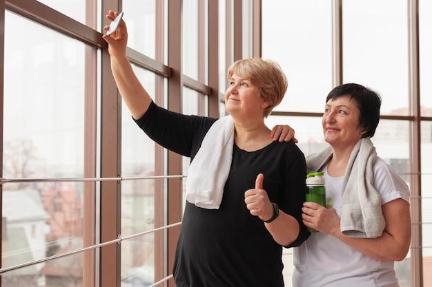 Frauen im fitnessstudio nehmen selfie