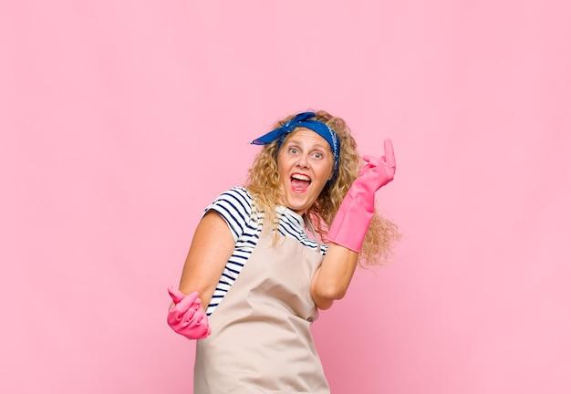 Frauen im mittleren alter, die sich sorglos, entspannt und glücklich fühlen, tanzen und musik hören, spaß an einem party-housekeeper-konzept haben
