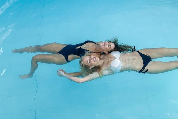 Frauen im poolwasser schöne glückliche frauen, die sich im schwimmbad schwimmen?