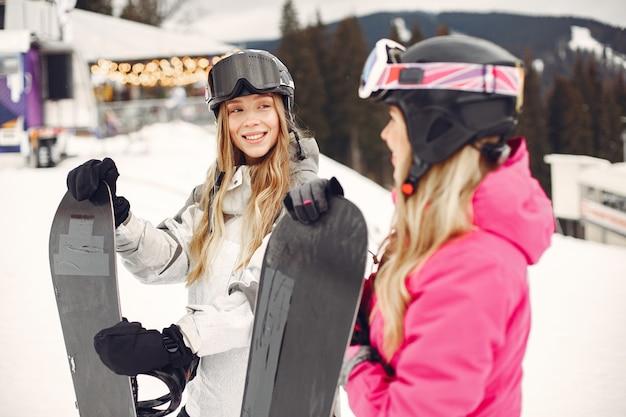 Frauen im snowboardanzug. sportlerinnen auf einem berg mit einem snowboard in den händen am horizont. konzept zum sport Kostenlose Fotos