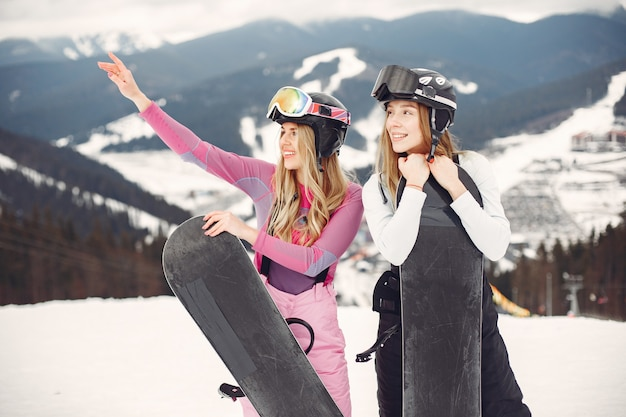 Frauen im snowboardanzug. sportlerinnen auf einem berg mit einem snowboard in den händen am horizont. konzept zum sport
