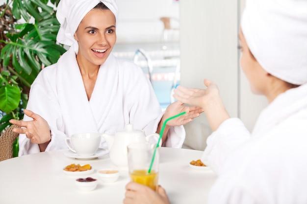 Frauen im spa. zwei schöne junge frauen im bademantel, die tee trinken und miteinander sprechen, während sie vor dem schwimmbad sitzen