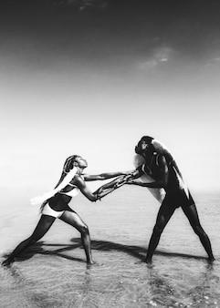 Frauen im weißen und schwarzen bikini und in den flügeln am strand