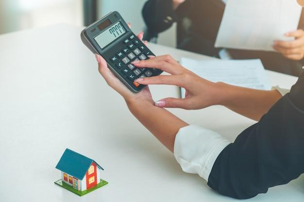Frauen-immobilienmakler, der mit taschenrechner und kleinem hausmodell arbeitet