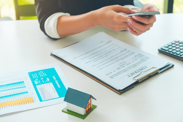 Frauen-immobilienmakler, der mit wohnungsbauvertrag arbeitet