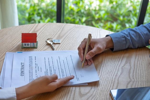 Frauen-immobilienmakler, der zeigt, wo auf dokument für kaufhausvertrag unterzeichnet wird