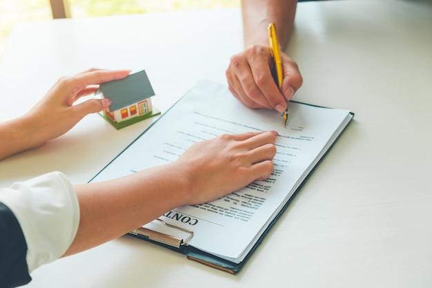 Frauen-immobilienmakler, der zeigt, wo man auf dokument für kaufhausvertrag unterzeichnet